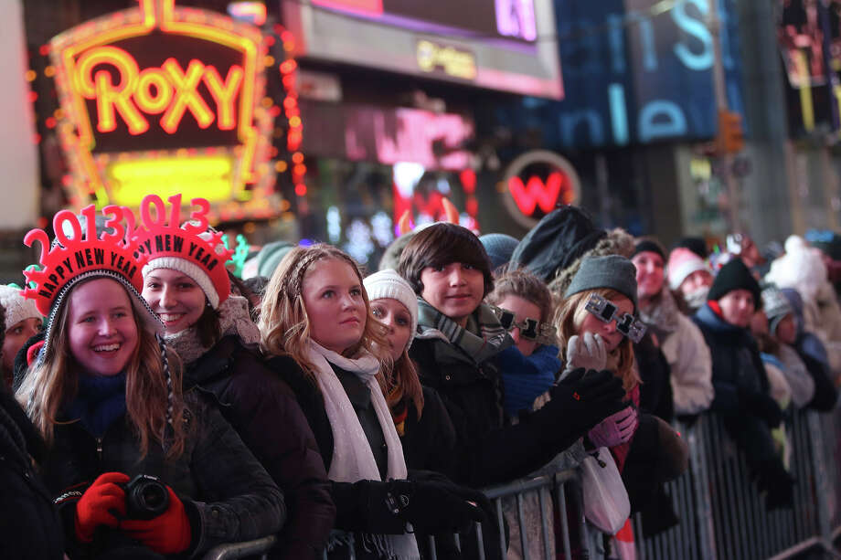 Vicky Tepper, left, and Nina Lober of Germany, join smile as they watch the warm up performance during Times Square New Year's celebration Monday, Dec. 31, 2012 in New York. Photo: AP