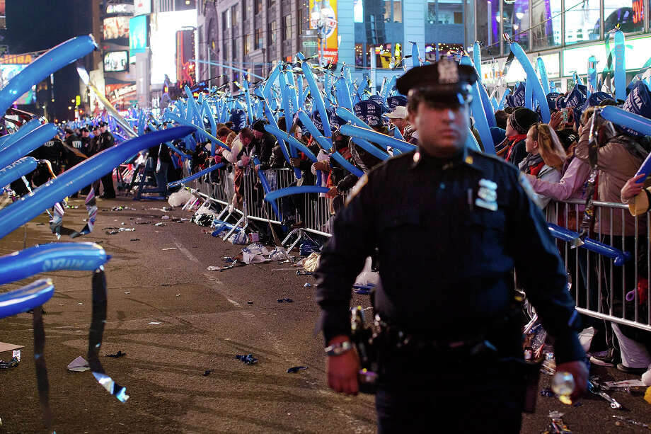 "FILE - In this Dec. 31, 2011 file photo, a police officer walks through a frozen zone in New York City's Times Square as revelers wave balloons in anticipation of midnight. The New York City police use an array of security measures for the event that turns the ""Crossroads of the World"" into a massive street party in the heart of Manhattan. Photo: AP"