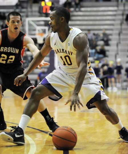UAlbany's Mike Black dribbles the ball to the hoop while guarded by Brown's Sean McGonagill during a