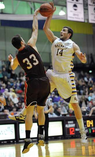 Brown's Tucker Halpern blocks a shot by UAlbany's Sam Rowley during a basketball game at the SEFCU A