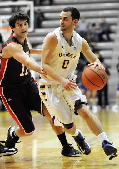 UAlbany's Jacob Iati dribbles the ball while guarded by Brown's Joe Sharkey during a basketball game