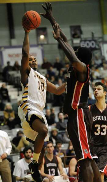 UAlbany's Mike Black drives to the hoop while guarded by Brown's Cedric Kuakumensah during a basketb