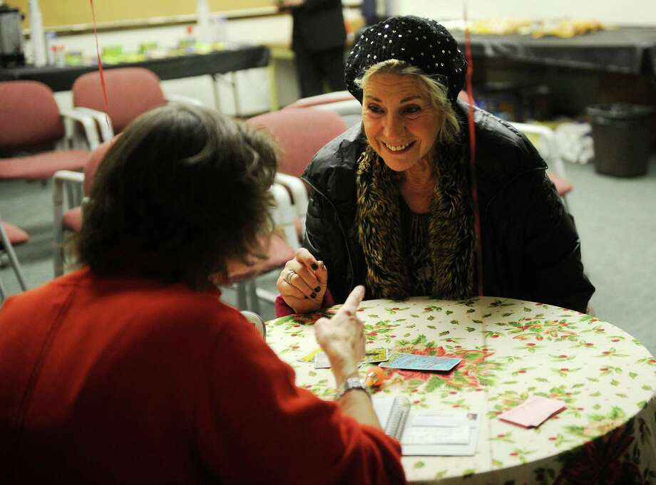 Trish Carruthers, facing, of Bournemouth, England, has her Tarot cards read by Susan Byrnes, of Westport, during First Night activities at Westport Town Hall on Monday, December 31, 2012. Photo: Brian A. Pounds, Connecticut Post / Connecticut Post