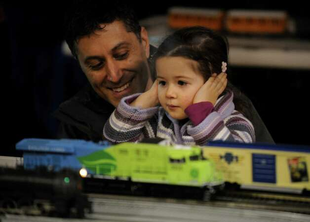 Izzy Bernie, 2, covers her ears as she checks out the model train display with her father Jon Bernie, of Weston, during First Night activities at the YMCA in downtown Westport on Monday, December 31, 2012. Photo: Brian A. Pounds, Connecticut Post / Connecticut Post