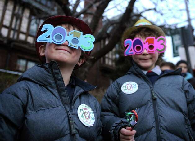 Brothers Dylan Richard Arouh, 4, left, and Aidan Arouh, 5, of Pound Ridge, NY, wear their 2013 glasses as they wait for a horse and buggy ride during First Night in downtown Westport on Monday, December 31, 2012. Photo: Brian A. Pounds, Connecticut Post / Connecticut Post