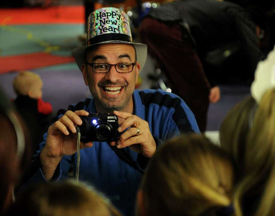 Bob Handelman of Westport snaps a family photo during First Night Westport/Weston activities at the TD Bank on Main Street in downtown Westport on Monday, December 31, 2012. Photo: Brian A. Pounds, Connecticut Post / Connecticut Post