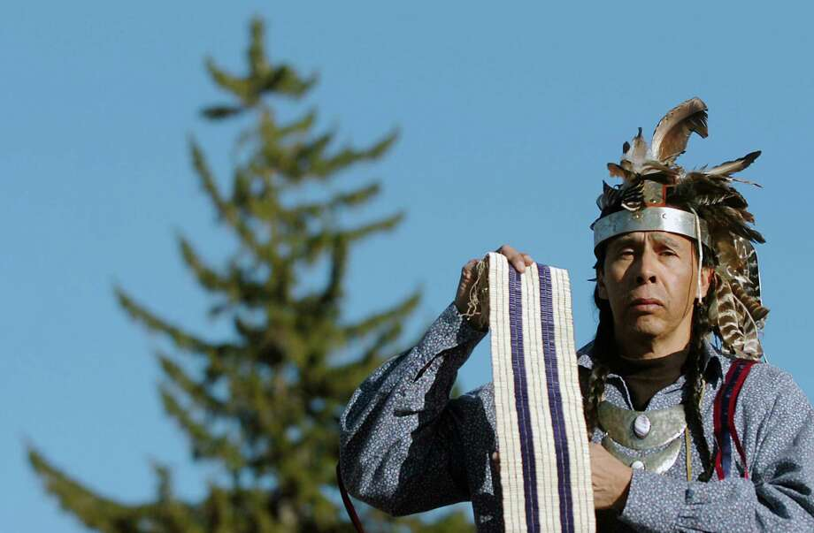Tadodaho Sidney Hill stands on the shore of Onondaga Lake holding a replica of the Two Row Wampum Belt, which tribal leaders from the Haudenosaunee nations (also known as the Iroquois)  point to as a symbol of as a key treaty made with Europeans in 1613.  It is considered by Haudenosaunee leaders as the basis relationships with foreign governments.  (John Berry/The Post-Standard) Photo: John Berry  / The Post-Standard