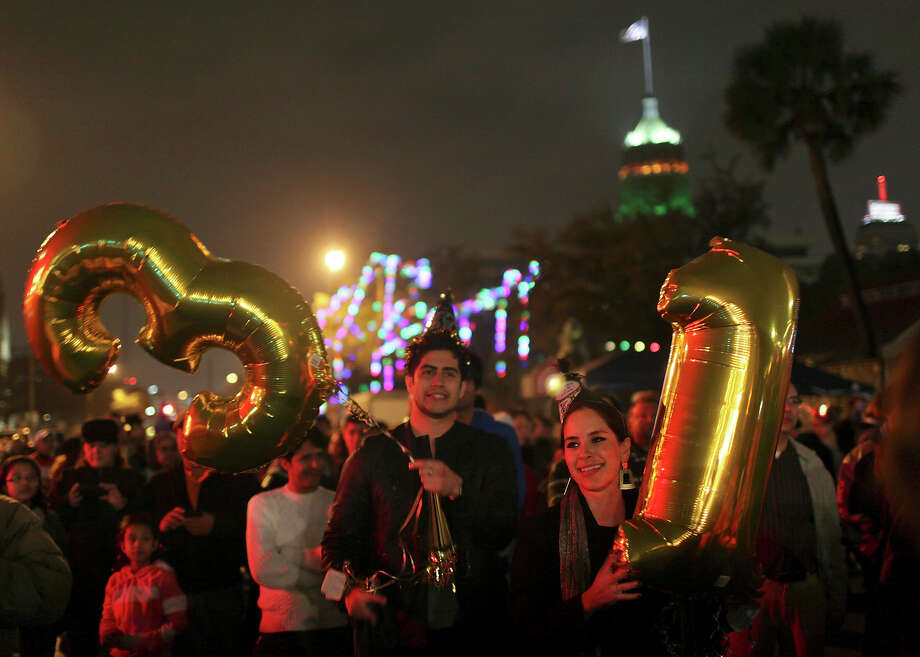 Alejandra Diaz and Xavier Mendoza hold balloons with the numbers 1 and 3 during the Celebrate San Antonio event to welcome in the new year. Although the evening was wet, revelers' spirits weren't dampened. Repeat attendees said a more modest crowd made for shorter beer lines. Photo: Edward A. Ornelas, San Antonio Express-News / © 2012 San Antonio Express-News