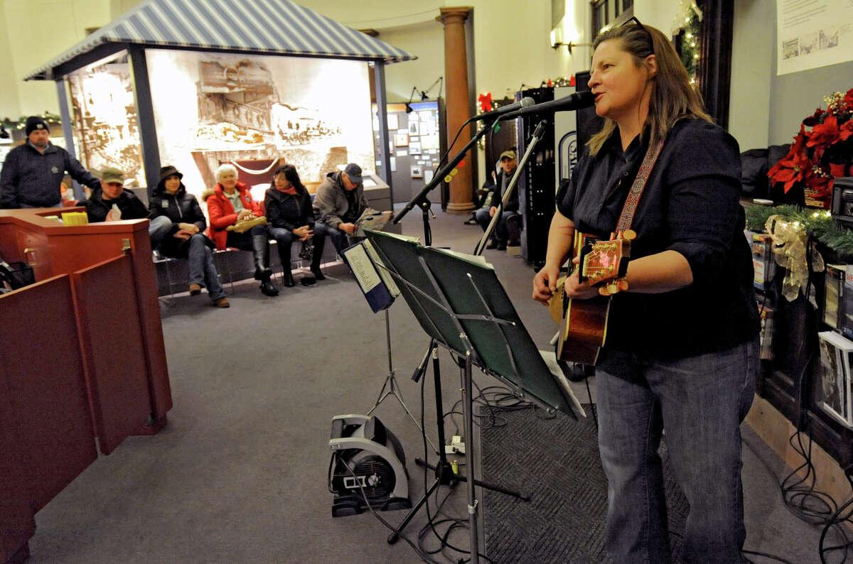 Spectators listen as singer, songwriter, guitarist Mikki Bakken sings a song at the Saratoga Visitors Center during First Night Saratoga on Monday Dec. 31, 2012 in Saratoga Springs, N.Y. (Lori Van Buren / Times Union)