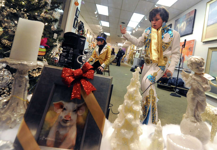 Matthew Boyce, 13, of Saratoga Springs impersonates Elvis in a storefront window during First Night Saratoga on Monday Dec. 31, 2012 in Saratoga Springs, N.Y. Matthew's little brother Spencer, 8, sits in the background. (Lori Van Buren / Times Union) Photo: Lori Van Buren