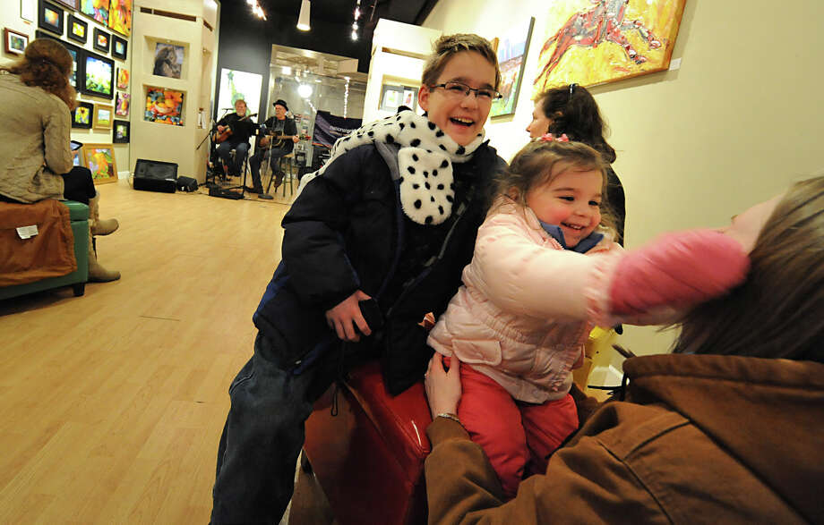 Brendan Smith, left, age 10, of Port Jervis and his sister Amanda Smith, right, play with their niece Kayli Decker, 2. as Low N' Lonesome play music at Flores Gallery during First Night Saratoga on Monday Dec. 31, 2012 in Saratoga Springs, N.Y. (Lori Van Buren / Times Union) Photo: Lori Van Buren