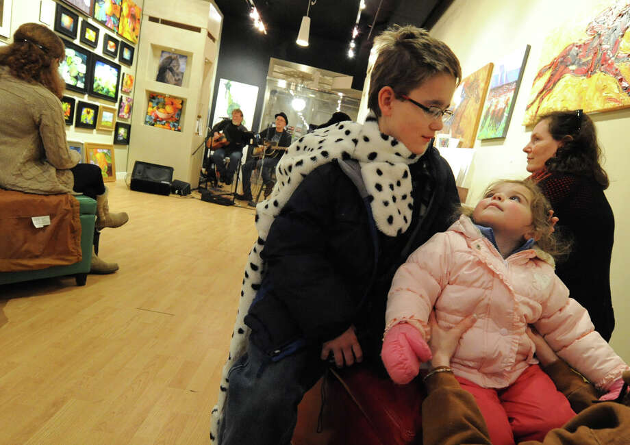 Brendan Smith, left, age 10, of Port Jervis looks at his niece Kayli Decker, 2, as Low N' Lonesome play music at Flores Gallery during First Night Saratoga on Monday Dec. 31, 2012 in Saratoga Springs, N.Y. (Lori Van Buren / Times Union) Photo: Lori Van Buren