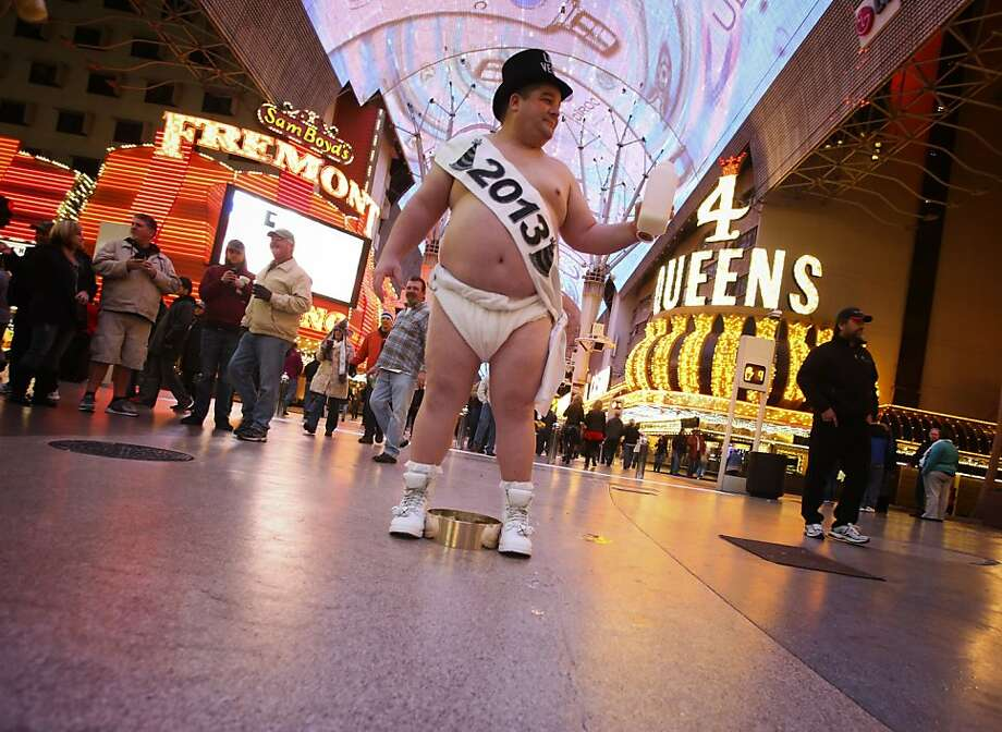 "Ronnie ""Tank"" Campbell of Fayetteville, N.C.  portrays Baby New Year on the Fremont Street Experience in Las Vegas, Monday, Dec. 31, 2012. ""This is what keeps me warm,"" said the 315 lb. truck driver, referring to his piña colada. (AP Photo/Las Vegas Review-Journal, Jeff Scheid) Photo: Jeff Scheid, Associated Press"