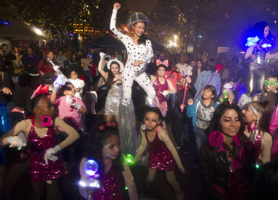 Children dance in a disco area at the Discovery Green New Year's bash.