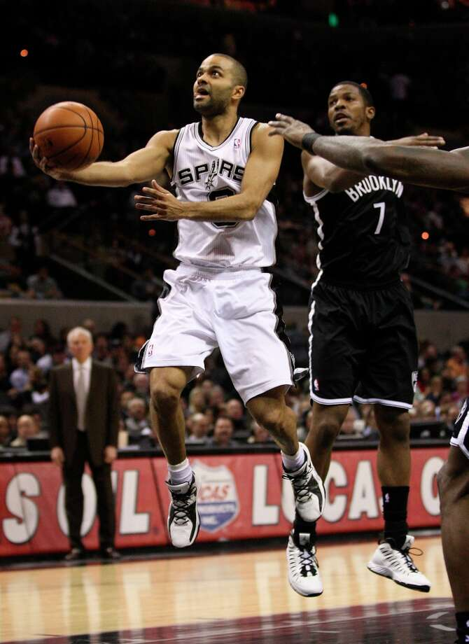 The Spurs' Tony Parker drives through the Nets' Joe Johnson during the first half at the AT&T Center, Monday, Dec. 31, 2012. Photo: Jerry Lara, San Antonio Express-News / © 2012 San Antonio Express-News