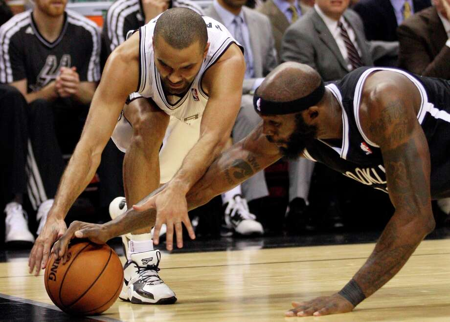 The Spurs' Tony Parker scrambles for the ball against the Nets' Reggie Evans during the first half at the AT&T Center, Monday, Dec. 31, 2012. Photo: Jerry Lara, San Antonio Express-News / © 2012 San Antonio Express-News