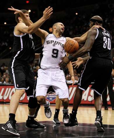 The Spurs' Tony Parker is stripped of the ball by the Nets' Brook Lopez, left, and Reggie Evans during the second half at the AT&T Center, Monday, Dec. 31, 2012. The Spurs won 104-73. Photo: Jerry Lara, San Antonio Express-News / © 2012 San Antonio Express-News