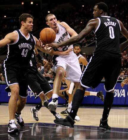 The Spurs' Nando De Colo passes around the Nets' Kris Humphries, left, and Andray Blatche during the second half at the AT&T Center, Monday, Dec. 31, 2012. The Spurs won 104-73. Photo: Jerry Lara, San Antonio Express-News / © 2012 San Antonio Express-News