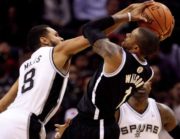 The Spurs' Patty Mills stuffs a shot by the Nets' C.J. Watson during the second half at the AT&T Center, Monday, Dec. 31, 2012. The Spurs won 104-73. Photo: Jerry Lara, San Antonio Express-News / © 2012 San Antonio Express-News