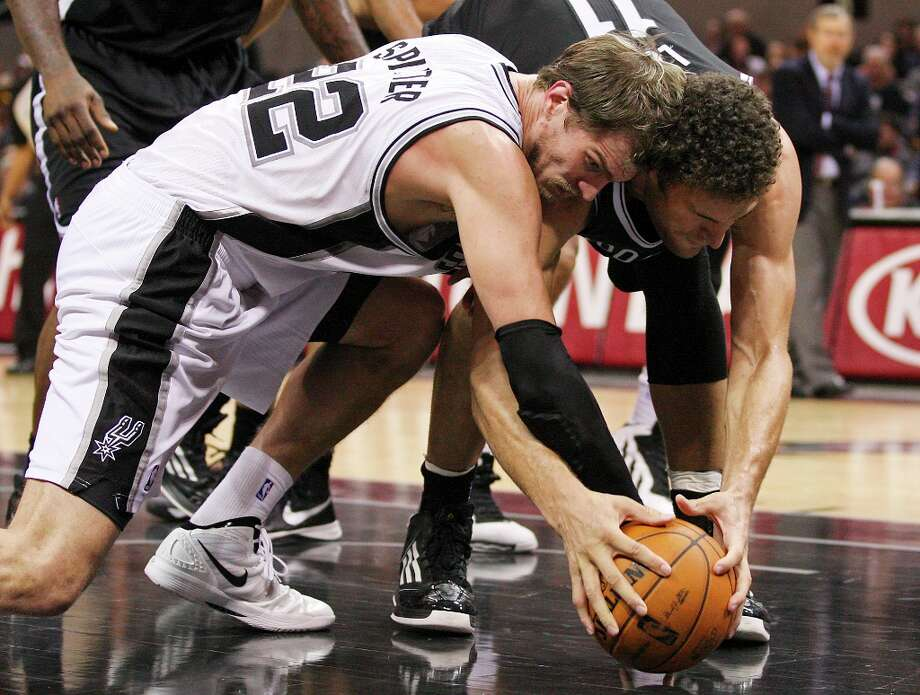 The Spurs' Tiago Splitter scrambles for the ball with the Nets' Brook Lopez during the second half at the AT&T Center, Monday, Dec. 31, 2012. The Spurs won 104-73. Photo: Jerry Lara, San Antonio Express-News / © 2012 San Antonio Express-News