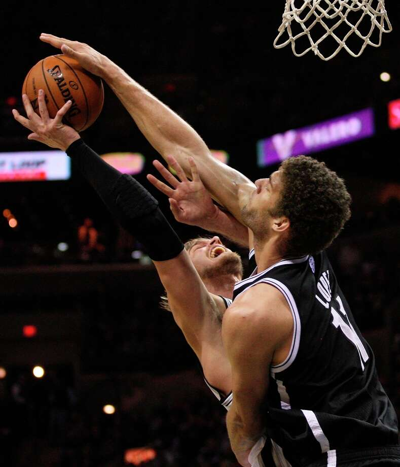 The Spurs' Tiago Splitter gets blocked by the Nets' Brook Lopez during the second half at the AT&T Center, Monday, Dec. 31, 2012. The Spurs won 104-73. Photo: Jerry Lara, San Antonio Express-News / © 2012 San Antonio Express-News