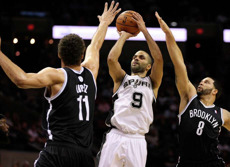 The Spurs' Tony Parker shoots between the Nets' Brook Lopez, left, and Deron Williams during the first half at the AT&T Center, Monday, Dec. 31, 2012. Photo: Jerry Lara, San Antonio Express-News / © 2012 San Antonio Express-News