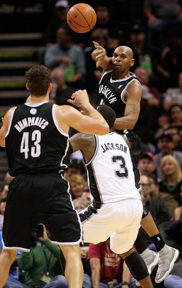 The Nets' Jerry Stackhouse passes over the Spurs' Stephen Jackson to teammate Kris Humphries during the first half at the AT&T Center, Monday, Dec. 31, 2012. Photo: Jerry Lara, San Antonio Express-News / © 2012 San Antonio Express-News