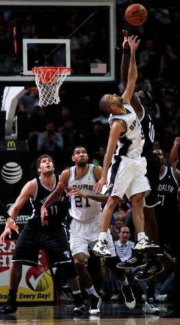 The Spurs' Tony Parker jumps for the ball with the Nets' Reggie Evans in first half at the AT&T Center, Monday, Dec. 31, 2012. Photo: Bria M. Webb, San Antonio Express-News / @2012 San Antonio Express-News