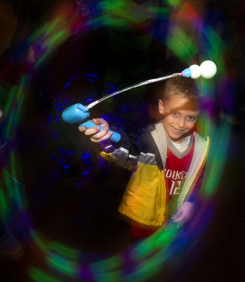 Cole Dobyanski spins his light toy around at Discovery Green.