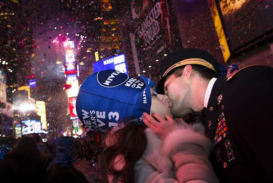 Newly engaged Sonja Babic, 30, of Texas, and National Guardsman John Cebak, 27, of Kentucky, share a kiss in Times Square at midnight on New Years Tuesday Jan. 1, 2013, in New York. With fireworks, concerts and celebrations from Hong Kong to New York, revelers welcome 2013 with hope for a better future after a year that thudded to a close with a disastrous storm, gun violence, and talk of economic turmoil from a looming fiscal cliff. This will be the first Times Square countdown in decades without Dick Clark, who died in April, and will be honored with a tribute concert and his name printed on pieces of confetti. (AP Photo/John Minchillo) Photo: John Minchillo, Associated Press