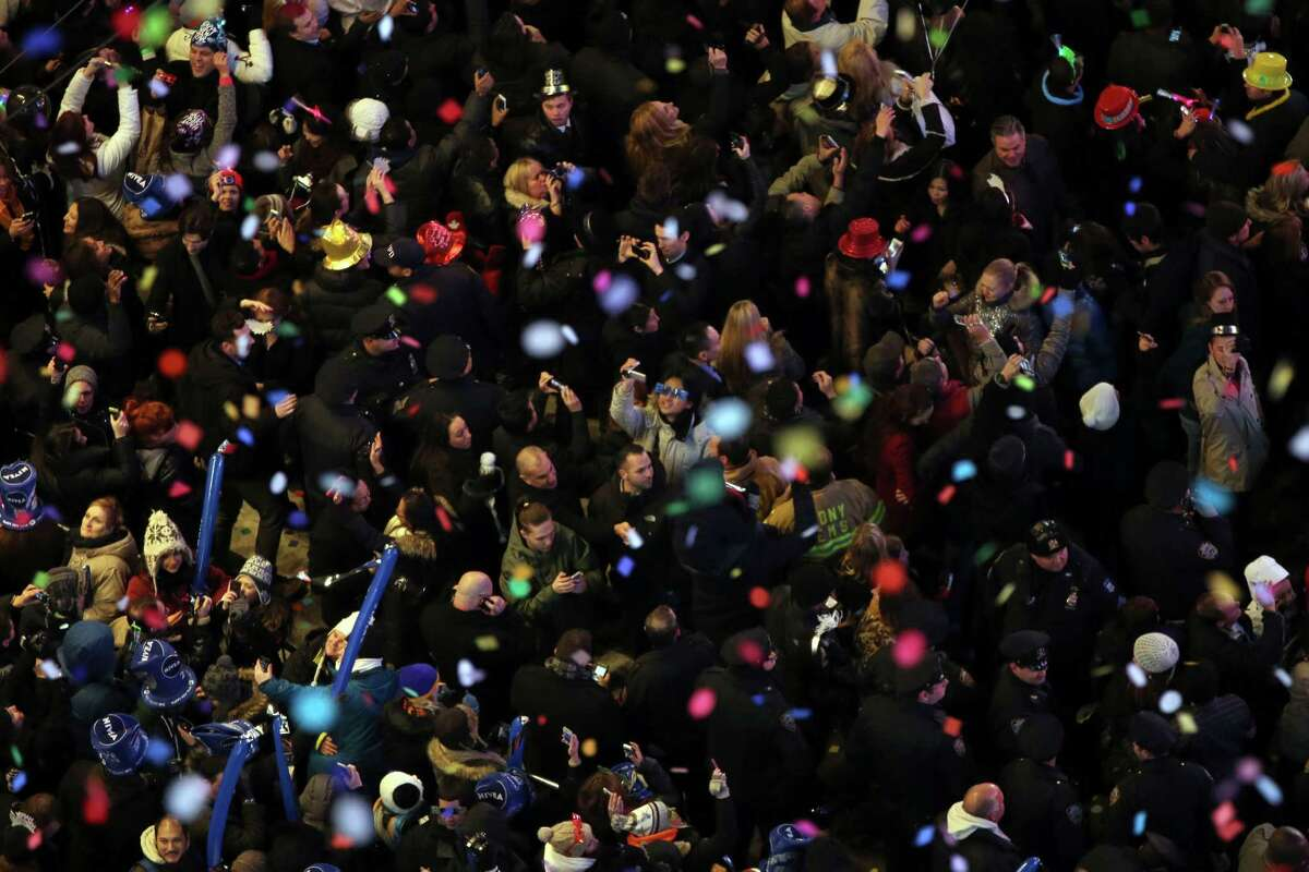 Revelers, center, take pictures as confetti flies over New York's Times Square after the clock strikes midnight during the New Year's Eve celebration as seen from the Marriott Marquis hotel Tuesday, Jan. 1, 2013 in New York.