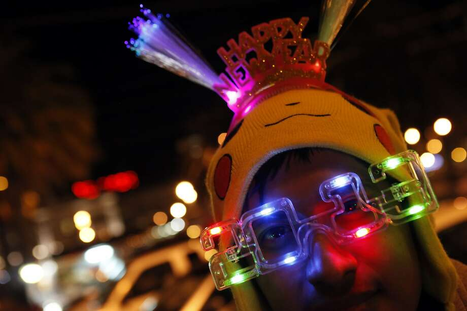 Alexis Torres of San Jose sells 2013 New Year's items on the Embarcadero. The Embarcadero was again the focal point of the New Year's celebrations as people from all over the Bay Area came to ring in the new year on Monday, December 31, 2012. Photo: Carlos Avila Gonzalez, The Chronicle