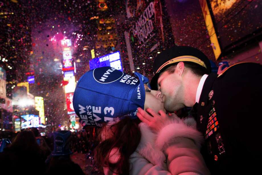 Newly engaged Sonja Babic, 30, of Texas, and National Guardsman John Cebak, 27, of Kentucky, share a kiss in Times Square at midnight on New Years Tuesday Jan. 1, 2013, in New York. With fireworks, concerts and celebrations from Hong Kong to New York, revelers welcome 2013 with hope for a better future after a year that thudded to a close with a disastrous storm, gun violence, and talk of economic turmoil from a looming fiscal cliff. This will be the first Times Square countdown in decades without Dick Clark, who died in April, and will be honored with a tribute concert and his name printed on pieces of confetti. Photo: AP