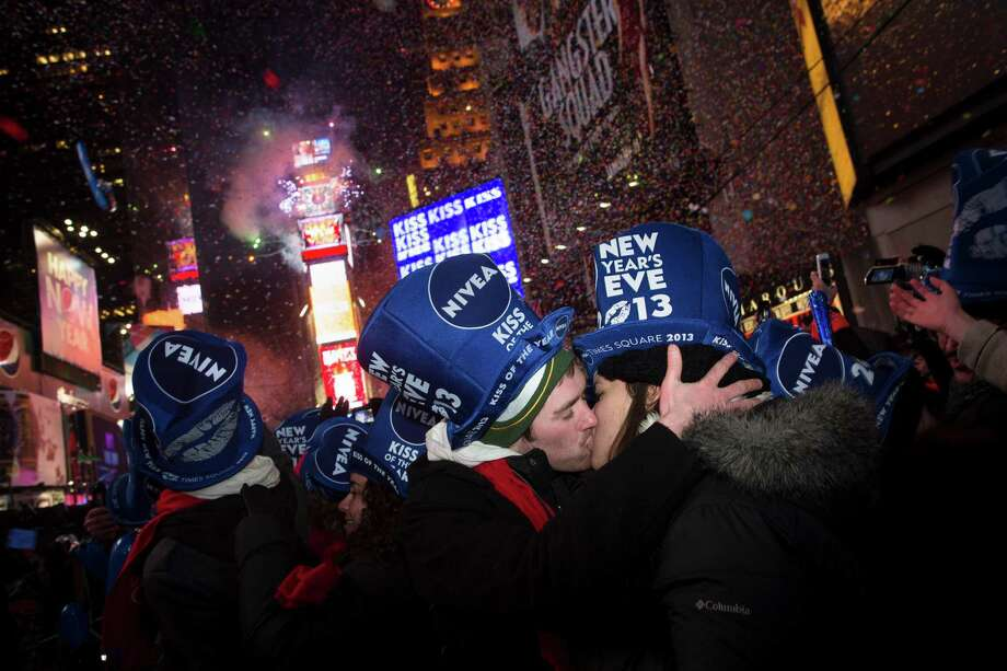 Jeremy Turnmeyer, 23, and Emily Mae Billington, 21, of Wisconsin, share a kiss in Times Square at midnight on New Years Tuesday, Jan. 1, 2013 in New York. With fireworks, concerts and celebrations from Hong Kong to New York, revelers welcome 2013 with hope for a better future after a year that thudded to a close with a disastrous storm, gun violence, and talk of economic turmoil from a looming fiscal cliff. This will be the first Times Square countdown in decades without Dick Clark, who died in April, and will be honored with a tribute concert and his name printed on pieces of confetti. Photo: AP