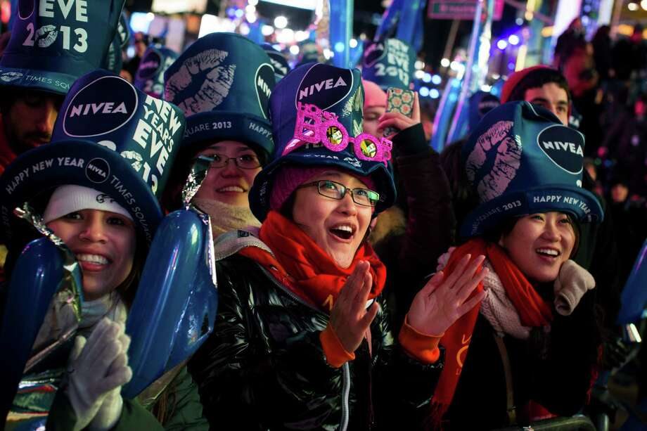 Qi Zhao, 25, of China, center, joins others in Times Square at the New Year's Eve celebration, Monday, Dec. 31, 2012, in New York. Photo: AP