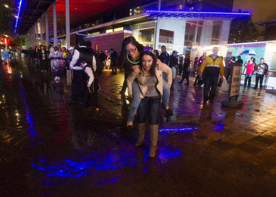 Ally Batista,  17,  carries her friend Paulina Nguyen,  16,  over a mud puddle on a wet night at Discovery Green.