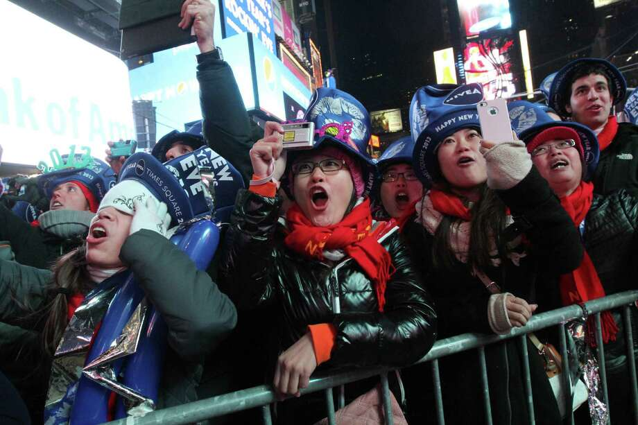 Qi Zhao, from China, foreground second from left, and others react seconds before midnight during the New Year's Eve festivities in New York's Times Square Monday Dec. 31, 2012. Photo: AP