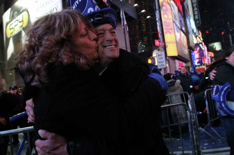 Rosemary Flescher, left, kisses her husband Joseph Flescher as they celebrate the new year shortly after midnight in New York's Times Square Tuesday Jan. 1, 2013.  The Flescher's, who have been married 24 years, live in Florida. Photo: AP