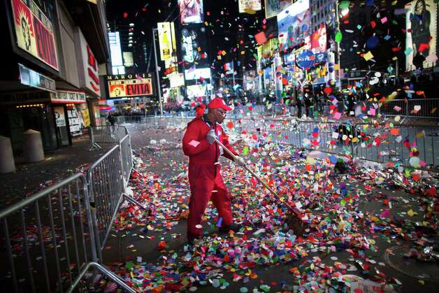 A worker clears confetti from a sidewalk in Times Square after midnight on New Years Tuesday Jan. 1, 2013, in New York. With fireworks, concerts and celebrations from Hong Kong to New York, revelers welcome 2013 with hope for a better future after a year that thudded to a close with a disastrous storm, gun violence, and talk of economic turmoil from a looming fiscal cliff. This will be the first Times Square countdown in decades without Dick Clark, who died in April, and will be honored with a tribute concert and his name printed on pieces of confetti. Photo: AP