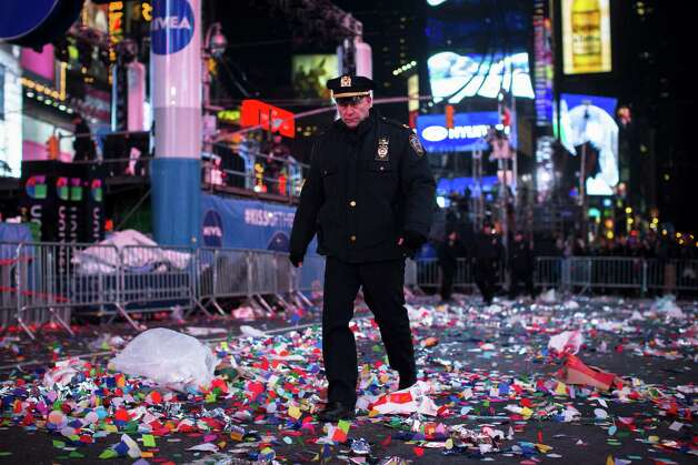 A NYPD officer walks through confetti and debris in Times Square after midnight on New Years Tuesday Jan. 1, 2013, in New York. With fireworks, concerts and celebrations from Hong Kong to New York, revelers welcome 2013 with hope for a better future after a year that thudded to a close with a disastrous storm, gun violence, and talk of economic turmoil from a looming fiscal cliff. This will be the first Times Square countdown in decades without Dick Clark, who died in April, and will be honored with a tribute concert and his name printed on pieces of confetti. Photo: AP