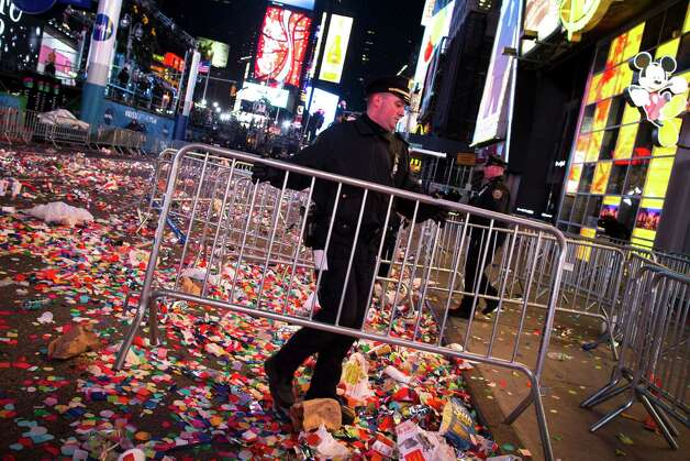 A NYPD officer clears barricades in Times Square after midnight on New Years Tuesday Jan. 1, 2013, in New York. With fireworks, concerts and celebrations from Hong Kong to New York, revelers welcome 2013 with hope for a better future after a year that thudded to a close with a disastrous storm, gun violence, and talk of economic turmoil from a looming fiscal cliff. This will be the first Times Square countdown in decades without Dick Clark, who died in April, and will be honored with a tribute concert and his name printed on pieces of confetti. Photo: AP