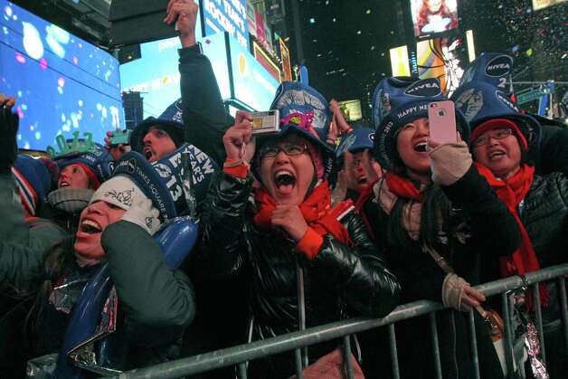 Qi Zhao, from China, foreground second from left, and others celebrate the new year in New York's Times Square Tuesday Jan. 1, 2013. Photo: AP
