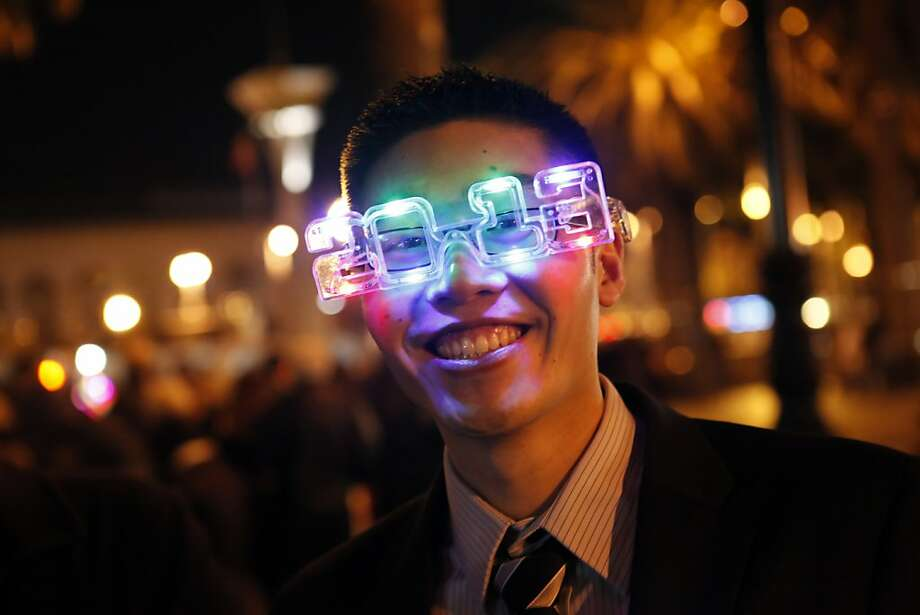 Henry Liu of Fremont smiles as he tries on a set of 2013 glasses in preparation for the party on the Embarcadero. The Embarcadero was again the focal point of the New Year's celebrations as people from all over the Bay Area came to ring in the new year on Monday, December 31, 2012. Photo: Carlos Avila Gonzalez, The Chronicle