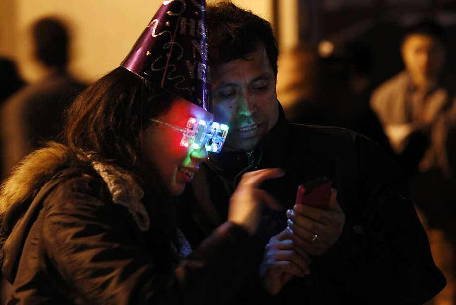 Seiko and Martin Alba check out photos they took on the Embarcadero as they wait for the New Year's Even party. The Embarcadero was again the focal point of the New Year's celebrations as people from all over the Bay Area came to ring in the new year on Monday, December 31, 2012. Photo: Carlos Avila Gonzalez, The Chronicle