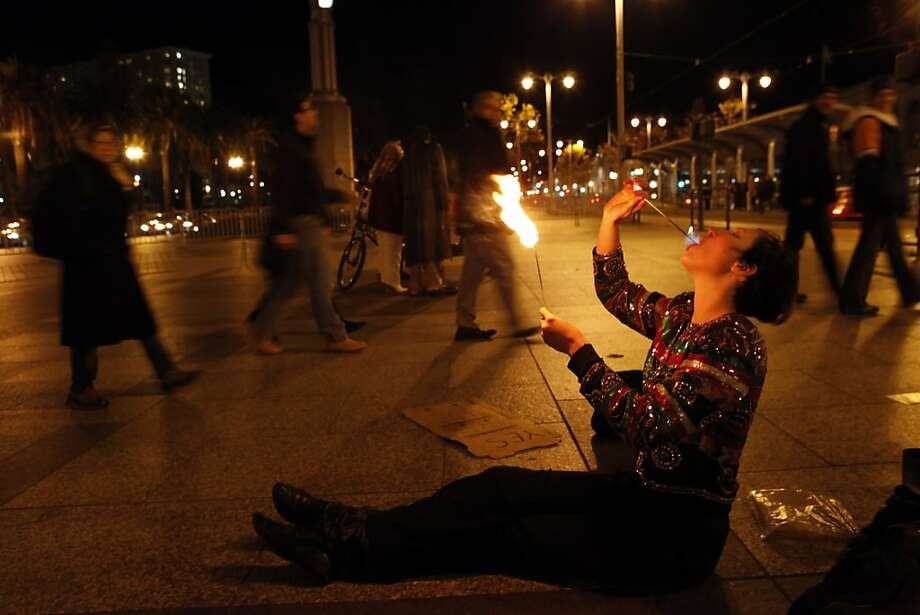 Taylor Way, a circus performer, eats fire for people gathering at the Embarcadero for the New Year's Eve celebrations. The Embarcadero was again the focal point of the New Year's celebrations as people from all over the Bay Area came to ring in the new year on Monday, December 31, 2012. Photo: Carlos Avila Gonzalez, The Chronicle