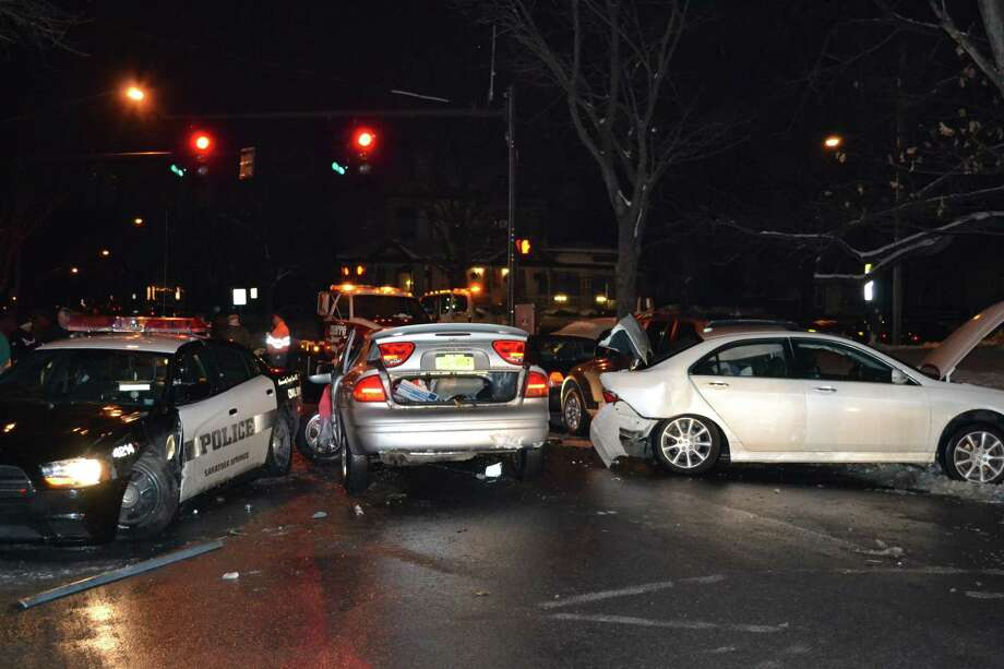 A chase through the streets of Saratoga Springs at the height of New Year's celebrations early Tuesday ended after six cars were damaged and three people were injured. The driver of the silver car, Aaron J. Elliott, is facing felony DWI and reckless endangerment charges, as well as more than a dozen other counts. (Saratoga Springs Police Department)