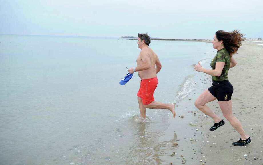 Sean Cahill, left, and Jill Rutsky, right, run into the Long Island Sound Tuesday morning, Jan. 1, 2013, at Compo Beach in Westport, Conn., during Temple Israel's 6th annual Polar Plunge. The plunge raised money for United Cerebral Palsy of New York City. Photo: Lindsay Perry, Perry / Stamford Advocate