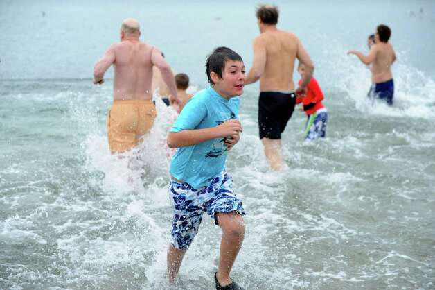 Sam Theriault, 11, runs out of the Long Island Sound Tuesday morning, Jan. 1, 2013, at Compo Beach in Westport Conn., after taking part in Temple Israel's 6th annual Polar Plunge. The event raised money for United Cerebral Palsy of New York City. Photo: Lindsay Perry, Perry / Stamford Advocate
