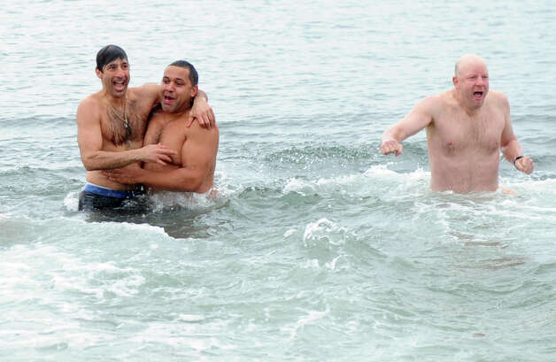 Frank Vartuli, left, and Tom Patterson, center, embrace after plunging into the Long Island Sound Tuesday morning Jan. 1, 2013, at Compo Beach in Westport Conn., during Temple Israel's 6th annual Polar Plunge. The plunge raised money for United Cerebral Palsy of New York City. Photo: Lindsay Perry, Perry / Stamford Advocate
