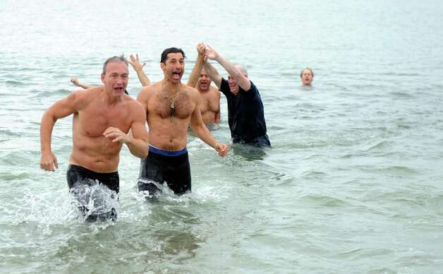 Temple Israel Polar Plunge participants run out of the Long Island Sound Tuesday morning, Jan. 1, 2013, at Compo Beach in Westport, Conn. The event raised money for United Cerebral Palsy of New York City. Photo: Lindsay Perry, Perry / Stamford Advocate
